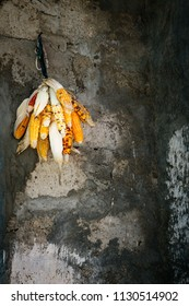 Drying food corn cobhanging on the wall of a poor village in Africa