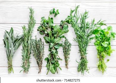 drying fresh herbs and greenery for spice food on white wooden kitchen desk background top view pattern
