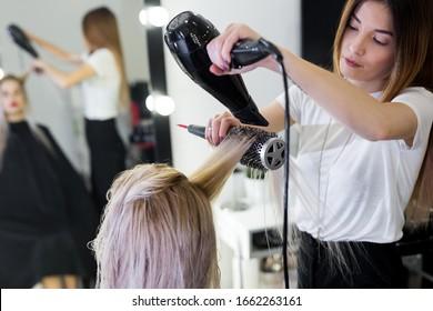 Trocknen Sie lange blonde Haare mit Haartrockner und Rundbürste