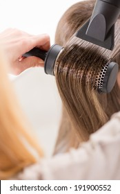 Drying long brown hair with hair dryer and round brush. Close-up.