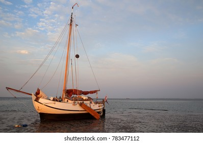 Drying of a sailboat on the tidal mudflats of the Wadden Sea, North Sea, Holland