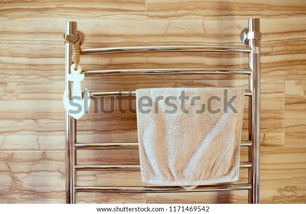 a drying towel dryer built into the wall of a bright bathroom. warm battery for drying clothes