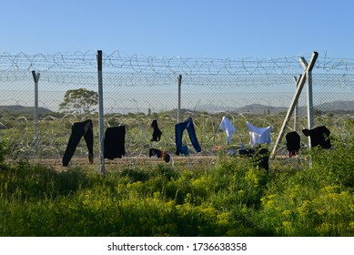 Drying washed clothes on a border fence with barbed wire. Difficult life conditions in transit refugee/migrant camp at the Greek-North Macedonian border. Families stuck on their way to Western Europe.