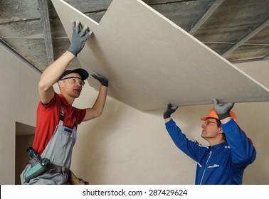 Drywall Installers. Men holding a gypsum board figured cut