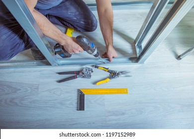 Drywall plaster stud crimpers in action. A person holding and using stud crimping tool in hand while building a metal drywall construction in a house during renovation