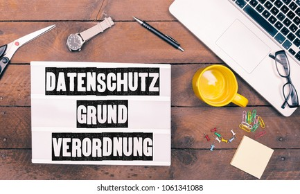 DSGVO, Datenschutzgrundverordnung (German for a new regulation effective May 2018 in European Union on general data protection/privacy) on paper, pencil for writing, grunge office desktop flat lay