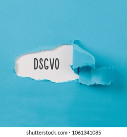 DSGVO (German for new regulation effective May 2018 in European Union on general data protection/privacy) message on torn blue paper revealing secret behind ripped opening.