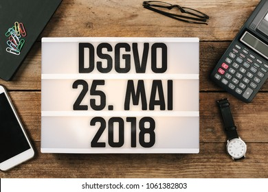DSGVO (German for new regulation effective May 2018 in European Union on general data protection/privacy) message in vintage style light box on office desktop, high angle birds eye view
