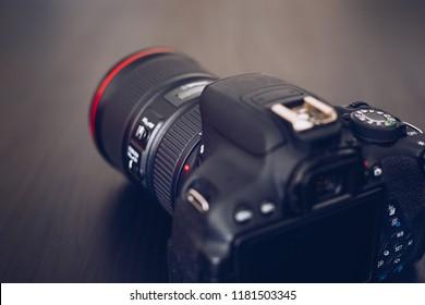 DSLR camera isolated on a black background. Black DSLR Camera isolated. Photo Camera or Video lens close-up on black background DSLR objective