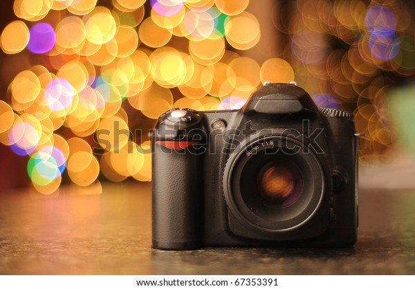 DSLR camera sitting on a black counter top with defocused bokeh background. Copyspace with room for your text.
