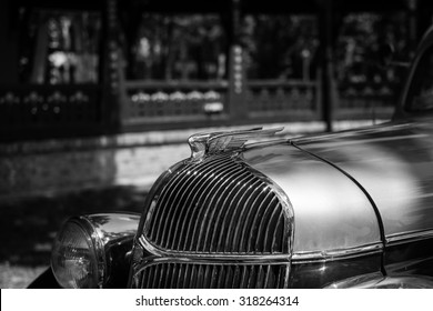 A DSLR photo of Chrysler from 1932 on Annual oldtimer car show Subotica 2015. The car was restored to the last screw. Beige roof with dark brown body.Focus on the Chrysler badge,black and white photo.