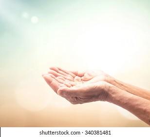 Dua concept: Muslim hands praying over amazing light background