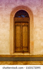 A dual color filtered view of an elaborately carved exterior door with a glass arch and a carved gypsum surround stands in front of a patterned, tiled floor in a restored traditional arabian house.