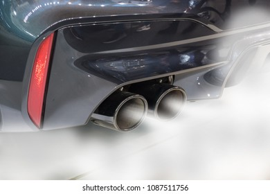 Dual exhaust pipe close up with combustion fumes coming out