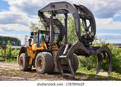 dual function grapple skidder stands on the ground outdoors