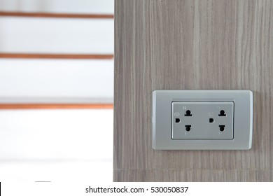 Dual silver gray empty electric sockets on wooden wall in front of stairs. Closed up.