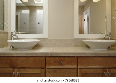 Dual Vessel Porcelain Sinks Are Set On A Wooden Vanity With A Tiled  Counter. There