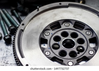 dual-mass flywheel with fastener parts in the background; shallow depth of field; copy space