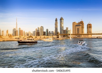 Dubai canal as seen during an amazing sunset light with boats already crossing it.