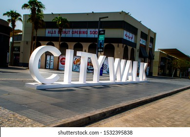 "Dubai, City walk - Oct 02. 2019.  Photo of the shopping street sign ""City Walk"" in large white letters taken from the street."