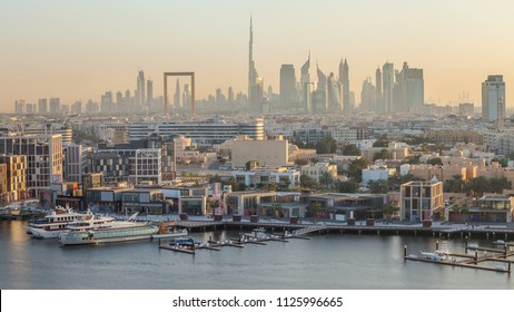 Dubai creek landscape timelapse with boats and yachts and modern buildings with downtown skyscrapers in the background during sunset. Aerial top view from above