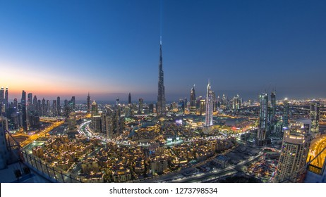 Dubai Downtown day to night transition  with Burj Khalifa and other towers panoramic view from the top before new year celebration in Dubai, United Arab Emirates. Lights turning on. Fisheye lens