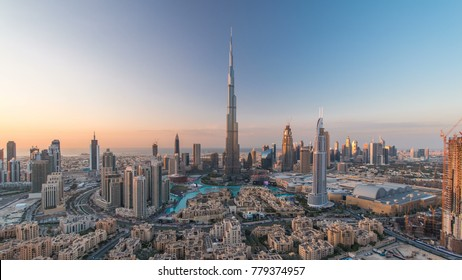 Dubai Downtown day to night transition timelapse with Burj Khalifa and other towers view from the top before new year celebration in Dubai, United Arab Emirates. Lights turning on. Zoom in