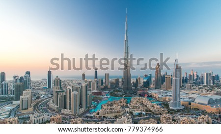 Dubai Downtown day to night transition timelapse with Burj Khalifa and other towers view from the top before new year celebration in Dubai, United Arab Emirates. Lights turning on. Pan right