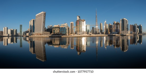 Dubai downtown at day reflected in water.