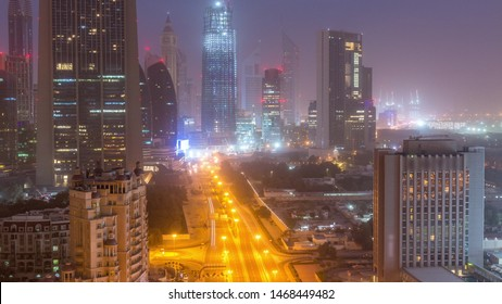 Dubai downtown skyline night to day transition aerial timelapse with traffic on highway, UAE. Top view from rooftop of skyscraper with modern towers near intersection of Al Saada street and Financial