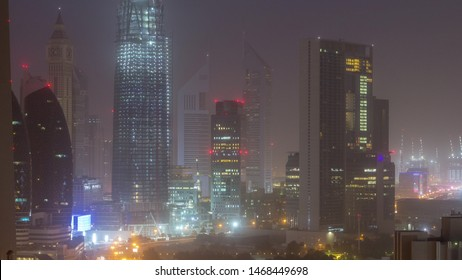 Dubai downtown skyline night to day aerial timelapse with traffic on highway, UAE. Top view from rooftop of skyscraper with modern towers with Al Saada street