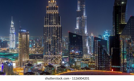Dubai downtown skyline night timelapse with tallest building and Sheikh Zayed road traffic, UAE. Aerial view from rooftop of skyscraper with illuminated modern towers