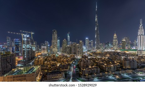 Dubai Downtown skyline night timelapse with Burj Khalifa and other towers paniramic view from the top in Dubai, United Arab Emirates. Traffic on circle road and fountains. Traditional and modern
