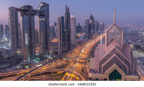 Dubai downtown skyline with tallest skyscrapers and busiest traffic on highway intersection night to day transition timelapse. Aerial view from above