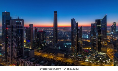 Dubai downtown skyline with tallest skyscrapers in financial center and traffic on highway night to day transition timelapse. Aerial view from above