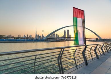 Dubai Downtown skyline with UAE national flag over the water canal at sunrise. Dubai, UAE.