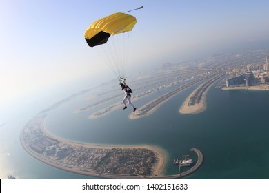 Dubai dream.Yellow extreme skydiving activity fun people on Dubai palm Jumeirah. Skydive Dubai jump travel. Yellow fun parachute jump. Summer  outdoor sky activity. Big goal
