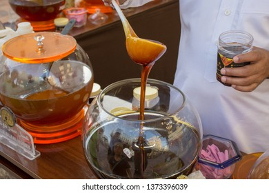 """Dubai, Dubai/United Arab Emirates - 4/6/2019: Man pouring Large bowls of sweet Yemen Duani, Sidr, Cinnamon, Ginger, and lots of other honey for sale at Global Market in Dubai, UAE."""