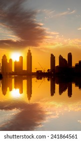 Dubai with golden silhouette of downtown against lagoon in United Arab Emirates