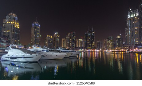 Dubai marina bay with yachts an boats timelapse hyperlapse. Skyscrapers illuminated by night reflected in water of canal