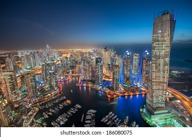 Dubai Marina at Blue hour, Glittering lights and tallest skyscrapers during a clear evening with Blue sky.