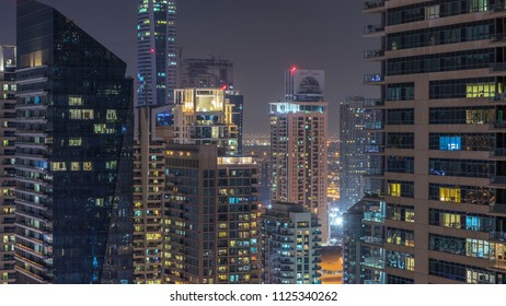 Dubai Marina and JLT at night timelapse, Glittering lights and tallest skyscrapers. Illuminated towers with light in windows and traffic on the road on background