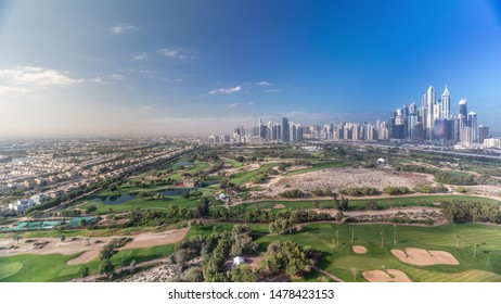 Dubai Marina with JLT skyscrapers and golf course morning timelapse, Dubai, United Arab Emirates. Aerial view from Greens district. Green lawn and cloudy sky