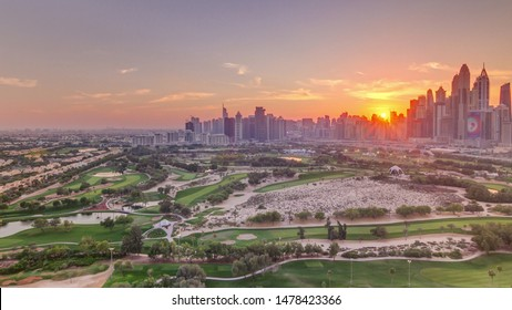 Dubai Marina and JLT skyscrapers and golf course sunset timelapse, Dubai, United Arab Emirates. Aerial view from Greens district. Rays of light and orange sky