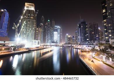 Dubai marina. Luxurious travel and living , business and finance theme. Night lights of marina bay. Illuminated construction site. Beautiful promenade.