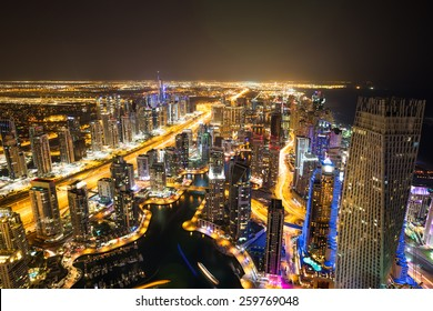 Dubai Marina night skyline. Dubai aerial view. Dubai skyscrapers. Cayan tower. Sheikh Zayed Road. Dubai Emaar properties buildings. Dubai from above. Dubai futuristic city.