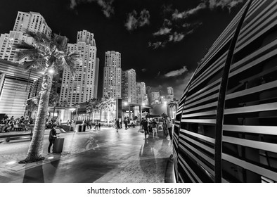 Dubai Marina skyline with city promenade at dusk.