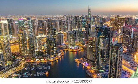 Dubai Marina with yachts in harbor and modern towers from top of skyscraper transition from day to night , Glittering lights and tallest skyscrapers during a clear evening with Blue sky.