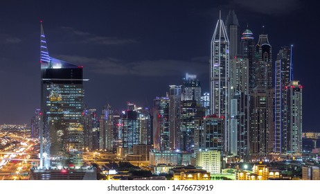 Dubai Media City and Dubai marina illuminated skyscrapers aerial night timelapse, United Arab Emirates. Modern towers with traffic on a highway
