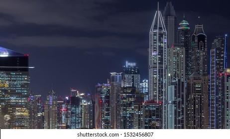 Dubai Media City and Dubai marina illuminated skyscrapers aerial night timelapse, United Arab Emirates. Modern towers with traffic on a highway